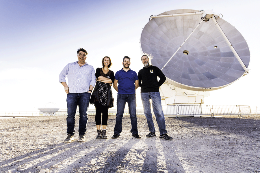 Group standing in front of ALMA telescope