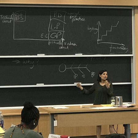 Salimah Samji teaching in front of blackboard