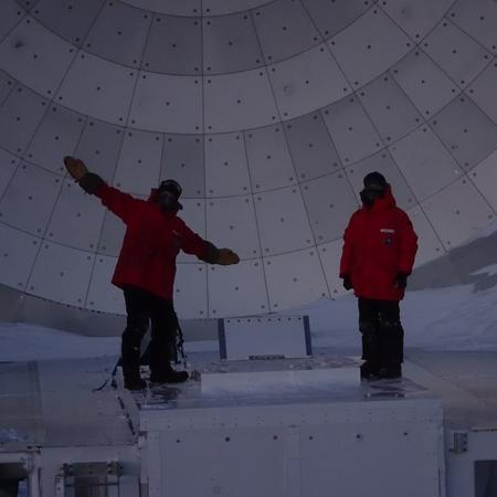 Andrew and Daniel on top of the South Pole Telescope receiver cabin. The picture shows the two SPT winter-over scientists after just having finished mounting the EHT optics in -60°C and darkness.