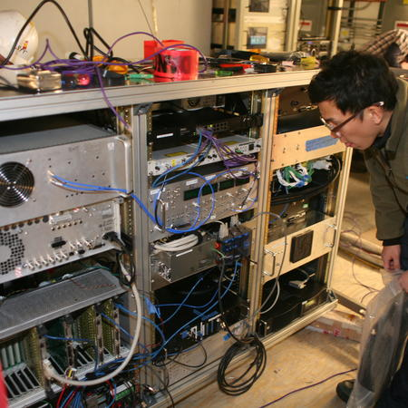 Junhan checking the EHT setup in the South Pole Telescope receiver electronics rack.