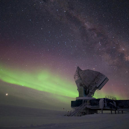 The South Pole Telescope illuminated by aurora australis and the Milky Way. Jupiter is brightly visible on the lower left, Saturn is located to the right of the telescope. The outside temperature is -60°C.