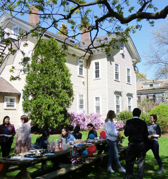 A group of about ten people enjoys food and conversation at a picnic table under a tree in the foreground, with a large cream-colored house in the background.