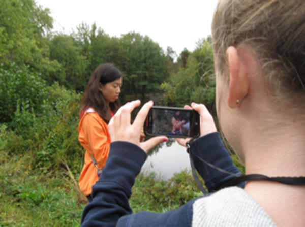 Students using ecoMOBILE on cell phones in a forest.