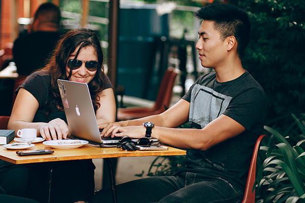 students at table with laptop