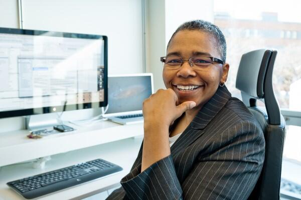 Latanya Sweeney sitting at her computer, smiling