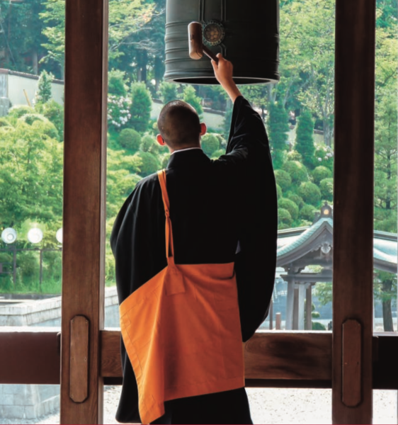 Man standing with back to viewer, wearing a long black and orange robe, and striking a large bell with a mallet