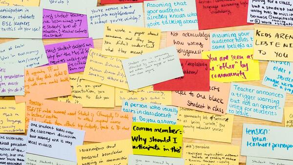 Overhead shot of overlapping multicolored cards with text about teaching on them