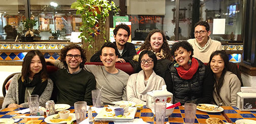 A group of graduate students gathered in a restaurant posing for a photo
