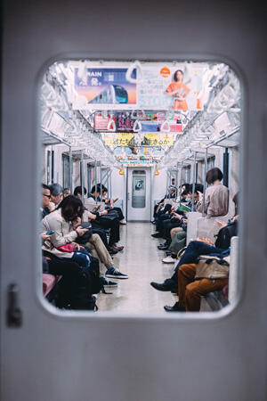 Stock photo of people sitting on the subway looking at their phones in Tokyo, Japan