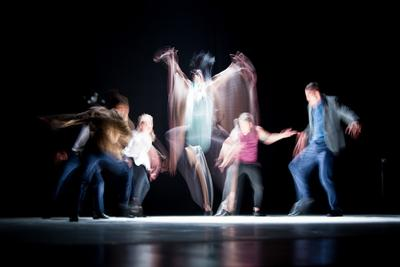 dancers blurred by motion on a stage