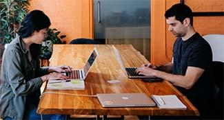 A man and a woman sitting at wooden table in an orange room and working on their laptops