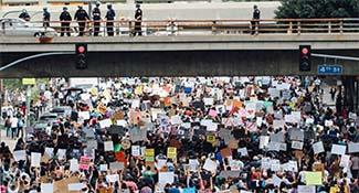 Crowd of people marching in protest under a bridge
