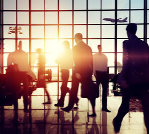 Black silhouettes of people in an airport with orange rising sun through windows