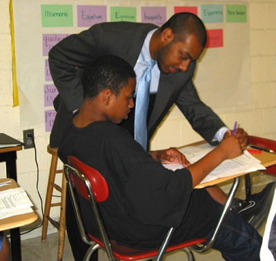 A teacher helping a student with an assignment at his desk