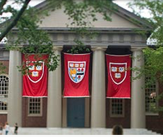 Harvard University building with three red flags displaying the school emblems between four columns