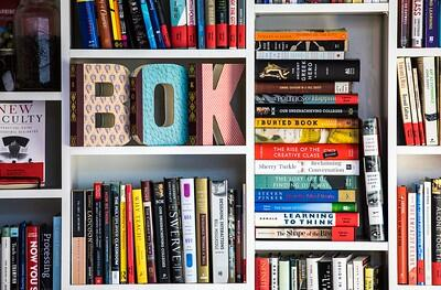 "white bookshelves with stacks of books and letters spelling out ""Bok"""