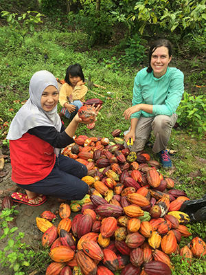 Image of Molly Leavens helping a farmer with the cacao harvest in South Sulawesi