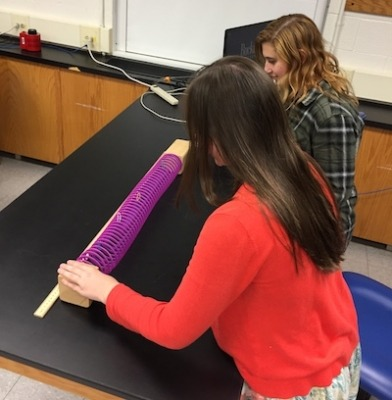 Student working with slinky to learn Hubble law
