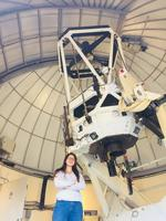 Image Description: Spotlight: Juliana García-Mejía in front of a telescope