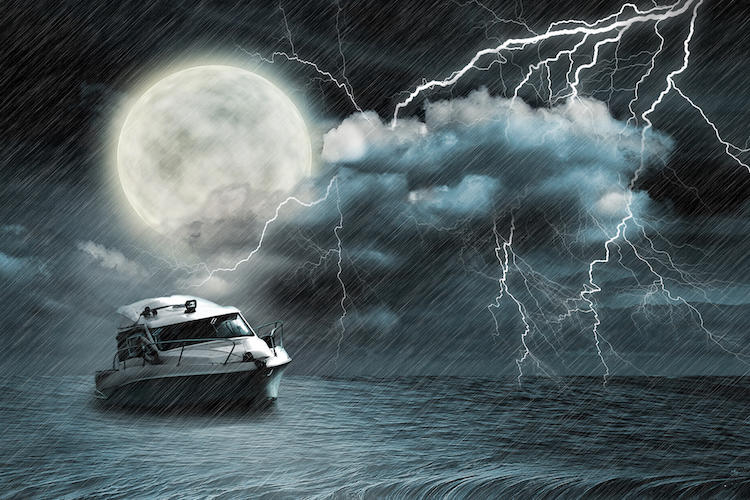 small yacht in lightning storm on the ocean under a large full moon