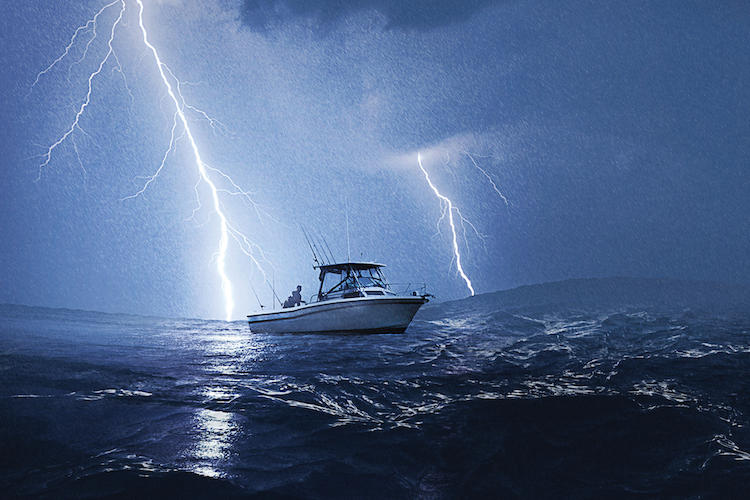 Man on a small fishing boat caught in a lightning storm on deep blue ocean