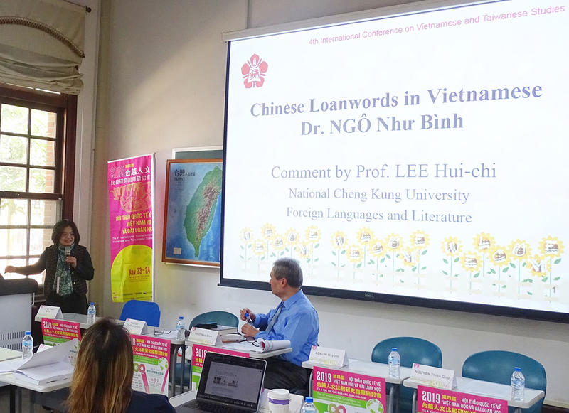 Dr. Ngo, seated in front of a projector screen bearing the title slide of his lecture on Chinese loanwords in Vietnamese, engages in conversation with a female colleague who stands at the podium speaking animatedly into a microphone.