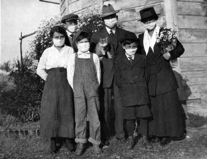 An American family, wearing masks, and their cat during the 1918 Spanish flu epidemic.