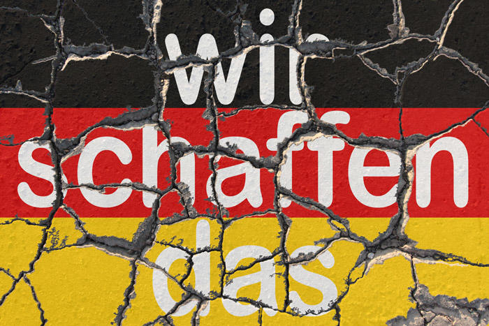 "Image of ""Wir schaffen das"" written on a cracked German flag"