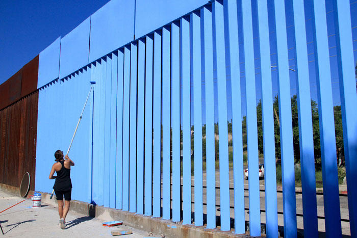 Image of an artist painting the porous border fence blue to match the sky