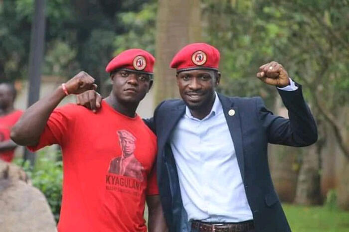 Bobi Wine and his driver, Frank, pose for the camera with raised fists