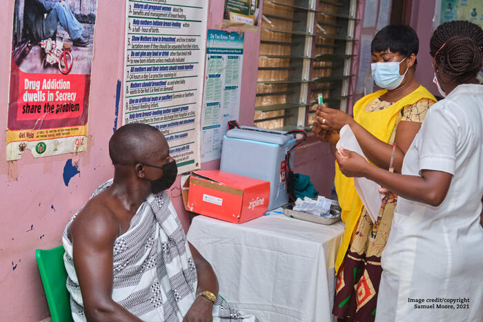 Two health care workers in Ghana draw up a covid vaccine for a patient sitting on a chair.