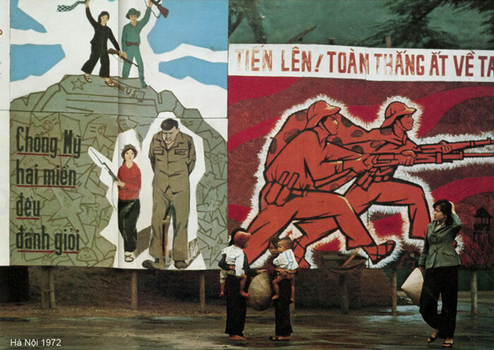 Vietnamese civilians gather in front of propaganda posters in downtown Hanoi, circa 1972.