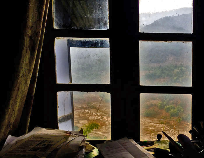 View from a window in Nagaland, looking out onto cultivated hillside terraces, to wooded hills beyond