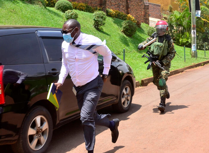 Journalist for Bobi Wine, in a suit, running from a police officer