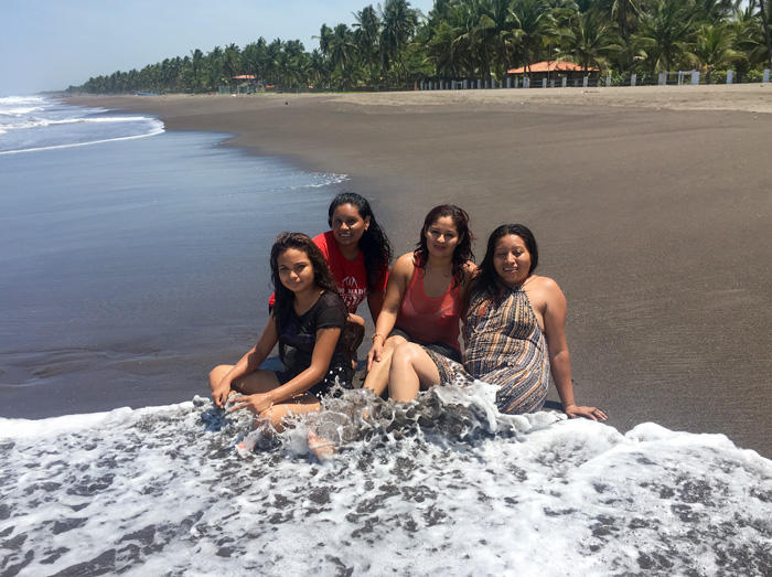 Image of four young women accused of homicide, sitting on the beach