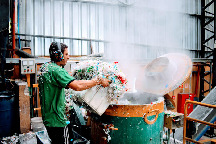 Image of a man working at a plastics recycling plant in Brazil
