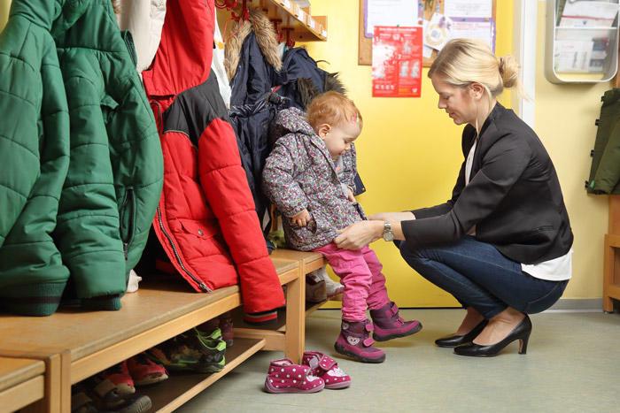 Image of woman helping child with coat in classroom