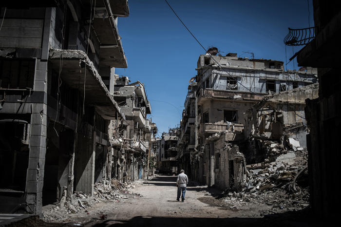 Image of Syrian refugee walking in downtown Homs, Syria