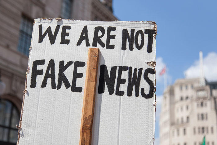 "Image of a sign with the words ""we are not fake news"" written on the back"