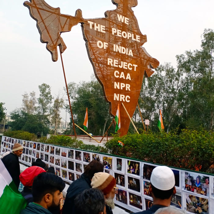 Image of people looking at a photo wall curated by the youth of Jamia Miliia Islamia University at Shaheen Bagh protests