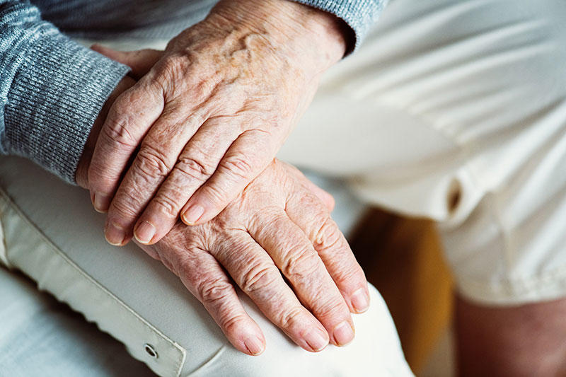 Image of elderly person's hands folded on lap