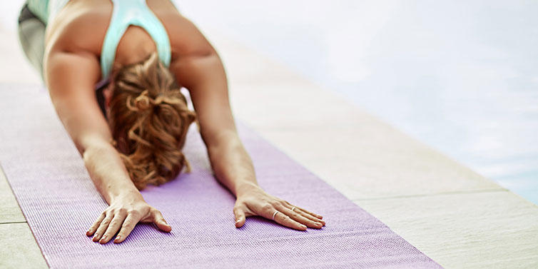 woman in yoga position with head down and arms stretched out on floor