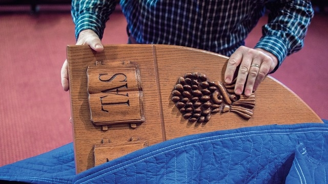Close up of hands putting wooden shield in blue blanket