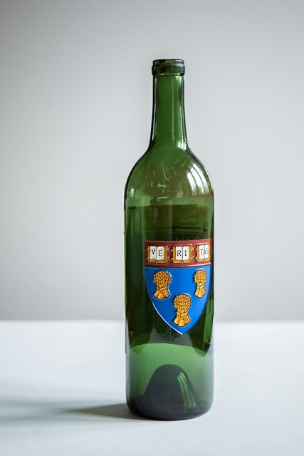 Full length view of green wine bottle with embossed former HLS shield