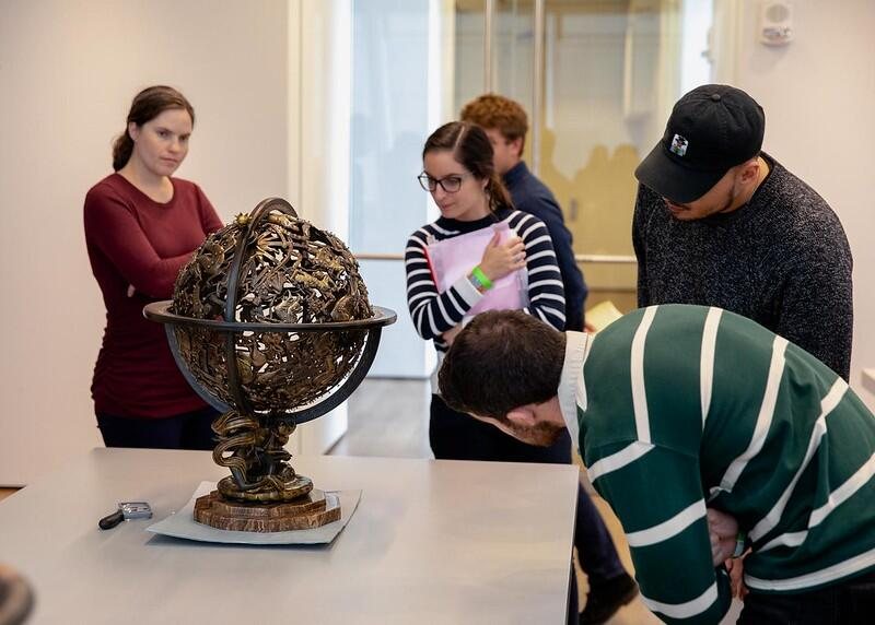 Students in a Bok Seminar observe a bronze sculpture on a table at the Art Museum