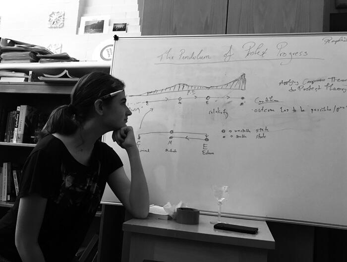 Raphaelle Soffe gazes at whiteboard drawings of her theory on protest progress