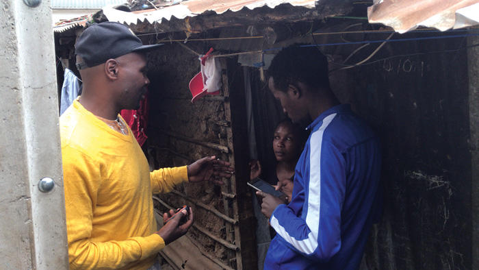 Image of a surveyor asking questions to resident in Mathare