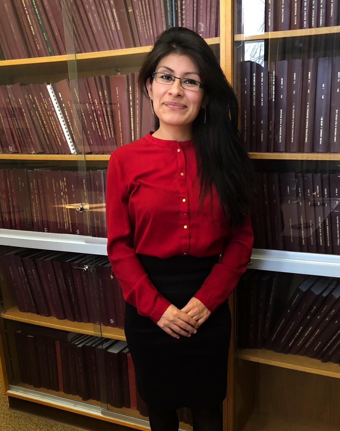 Emerita Mendoza Rengifo standing in front of a tall bookcase wall, wearing a red shirt and drak brown hair down.