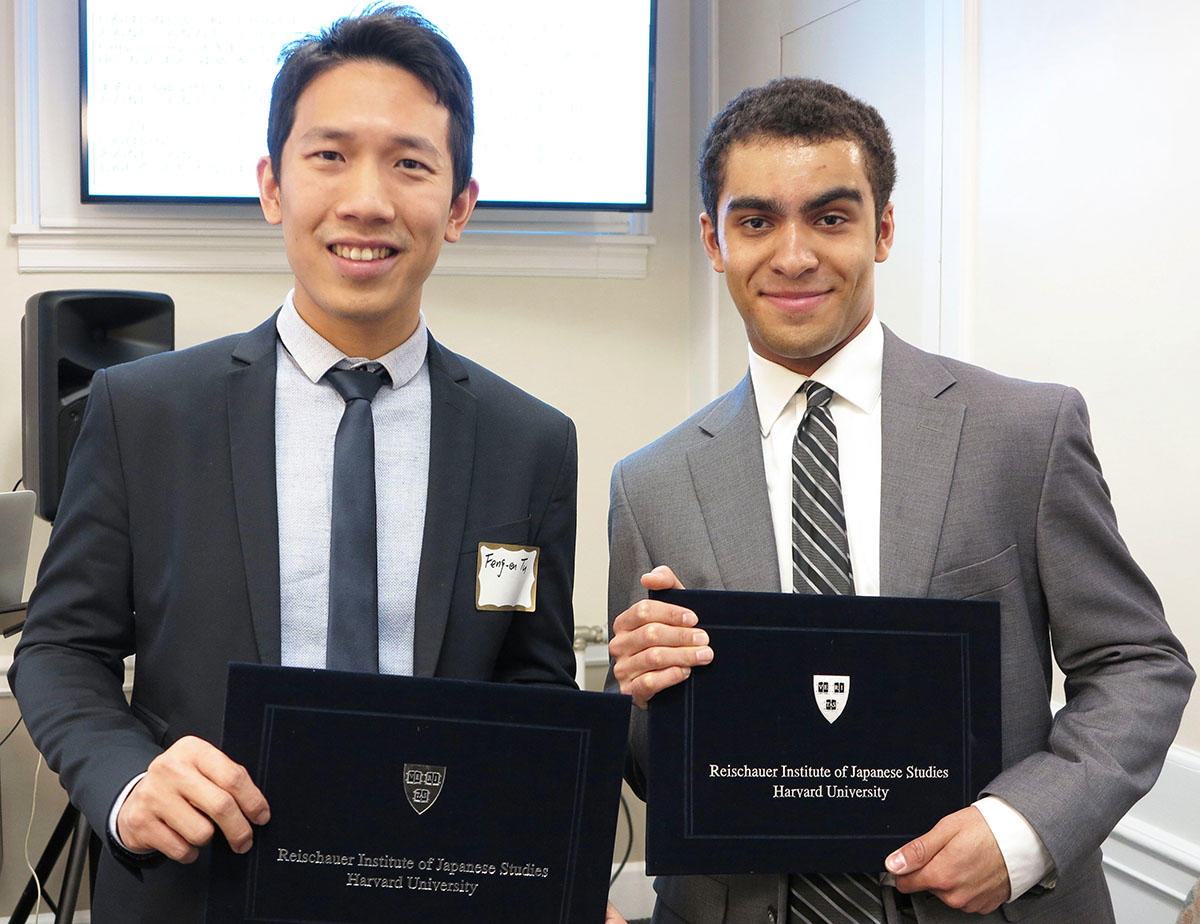 Feng-en Tu, left, and Devon Gunter, right, both wearing suits, stand together holding their Noma-Resichauer award certificates and smiling.