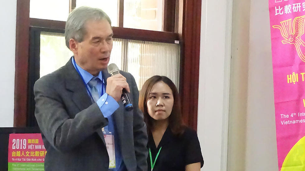 Dr. Binh Ngo holds a microphone and speaks at the front of a conference room. Behind him stands a young woman, listening to his talk.
